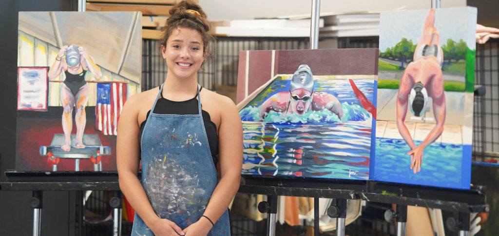 A Jessi Snover standing in front of three paintings of swimmers