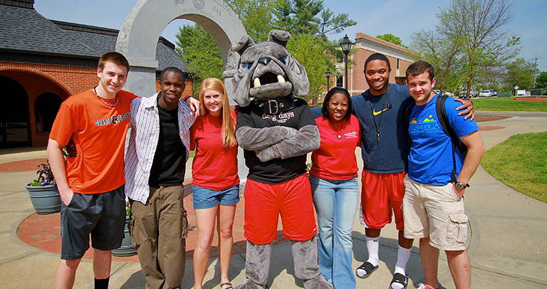GWU students standing in front of arch on campus with mascot
