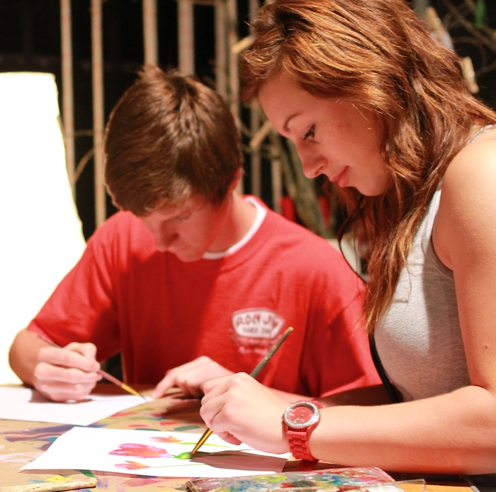 A male and female student create paintings at Crossroads Camps.