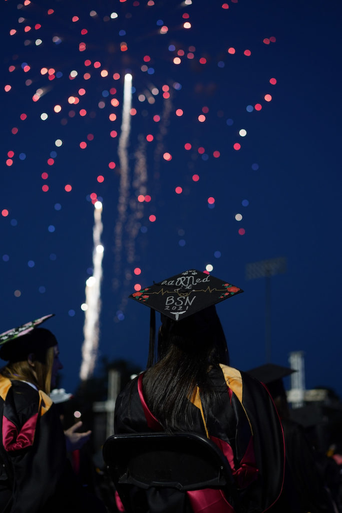 Fireworks explode over the heads of graduates