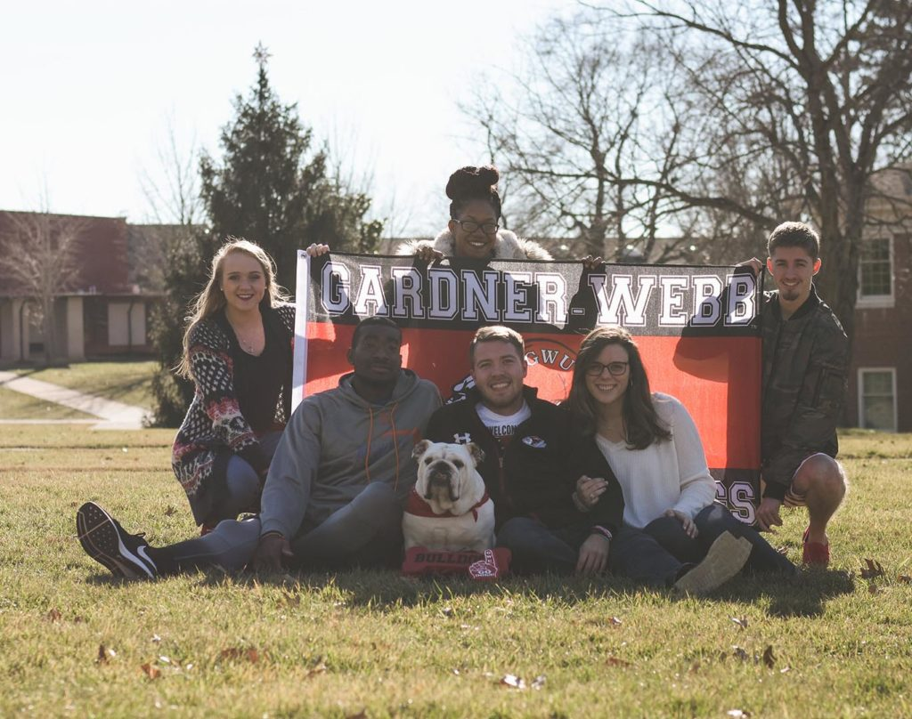 Roebuck with group of students and Gardner-Webb flag
