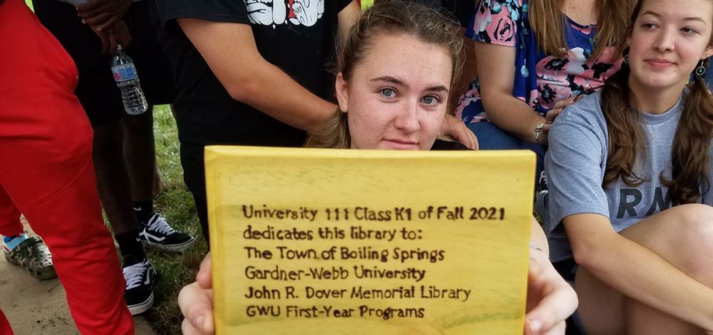A student holds up a sign for the Little Free Library Box